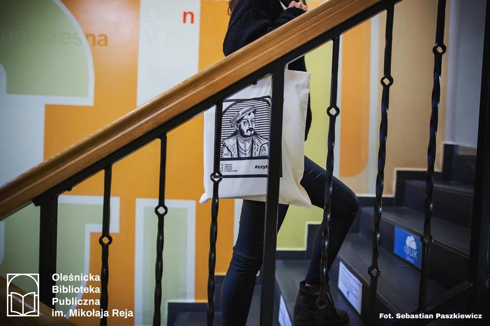 Czytelniczka z torbą promocyją oleśnickiej Biblioteki wchodząca po schodach do wypożyczalni