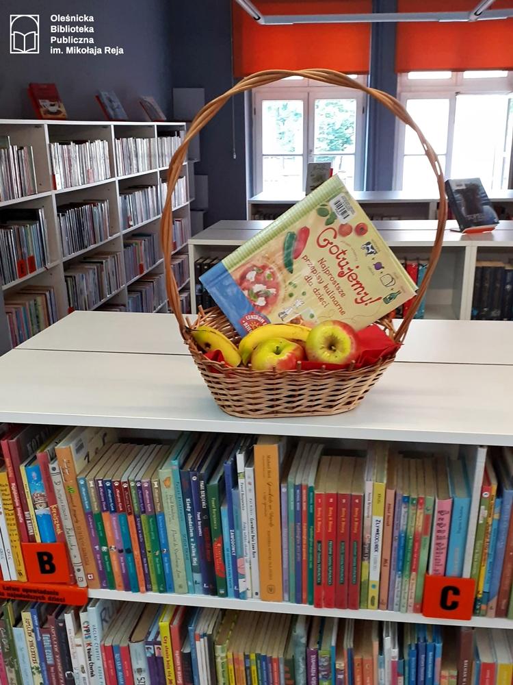 Książka kucharska w koszyczku z owocami ustawiona na regale bibliotecznym