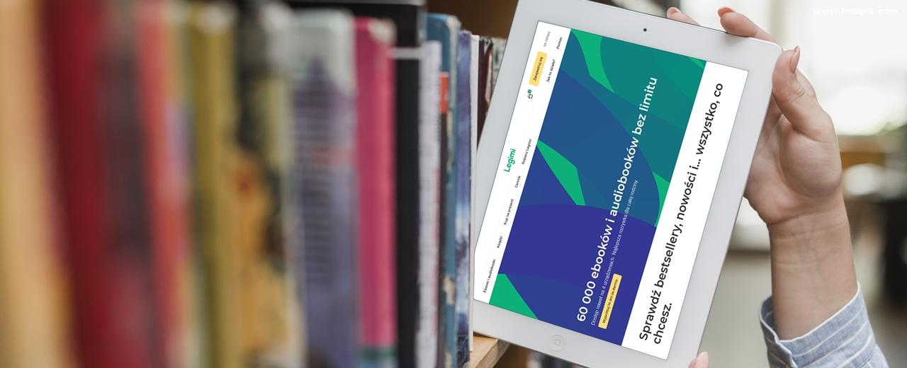 Dłonie wyciągające tablet z pomiędzy książek na regale bibliotecznym